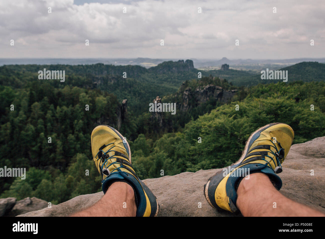 Germany, Saxony, Elbe Sandstone Mountains, man's feet on a hiking trip sitting on rock - Stock Image