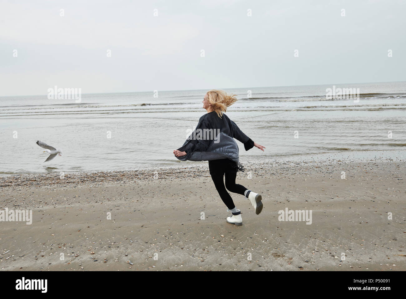 Netherlands, happy blond young woman running on the beach - Stock Image