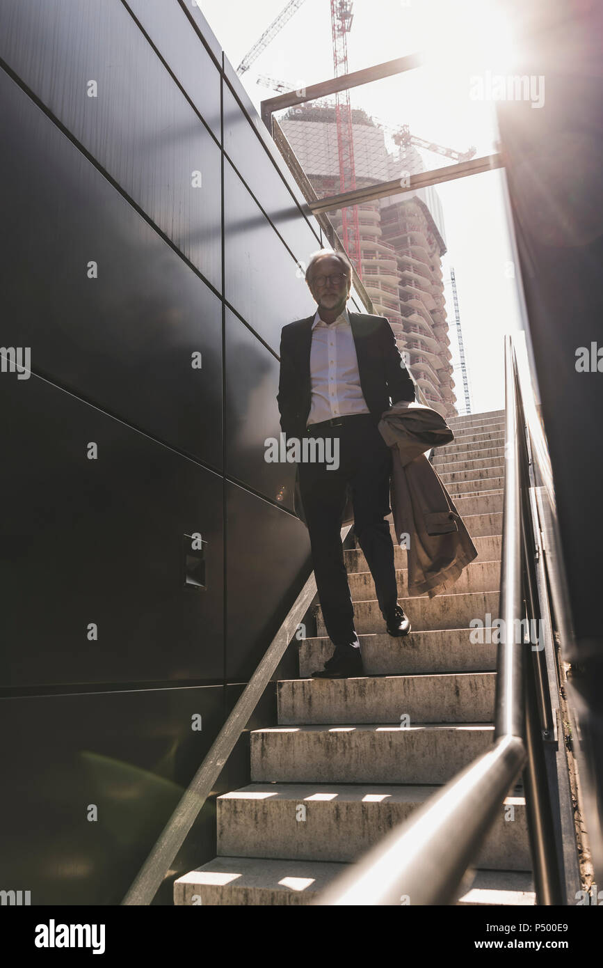 Mature businessman walking on staircase in the city - Stock Image