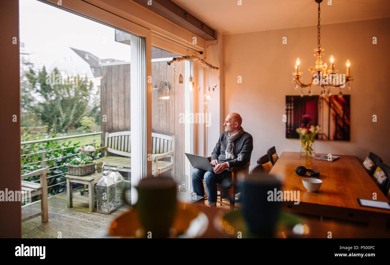 Senior man sitting at home, using laptop - Stock Image