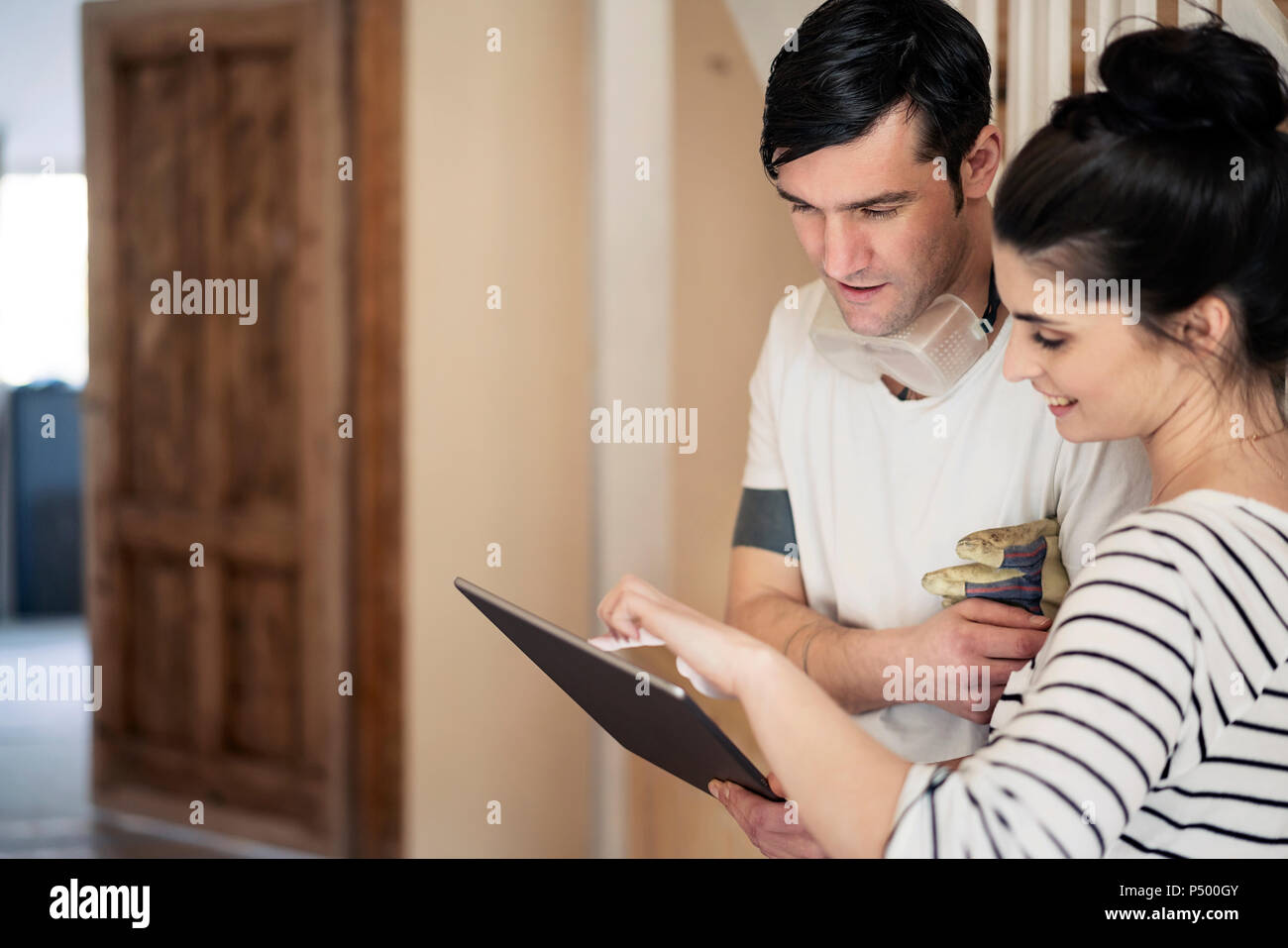 Young couple refurbishing new home, using digital tablet - Stock Image