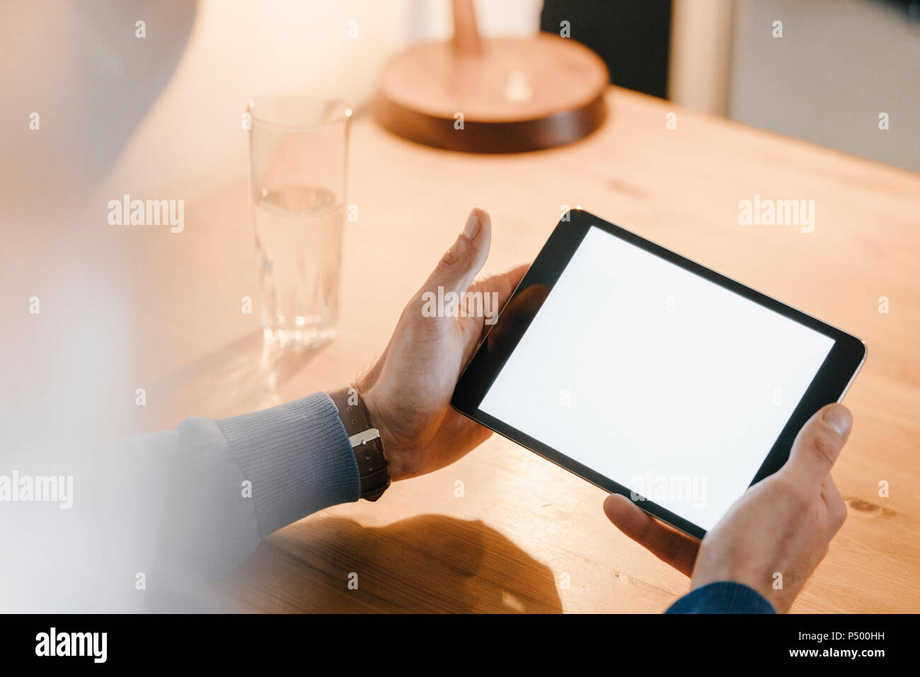 Close-up of man in a cafe holding tablet - Stock Image