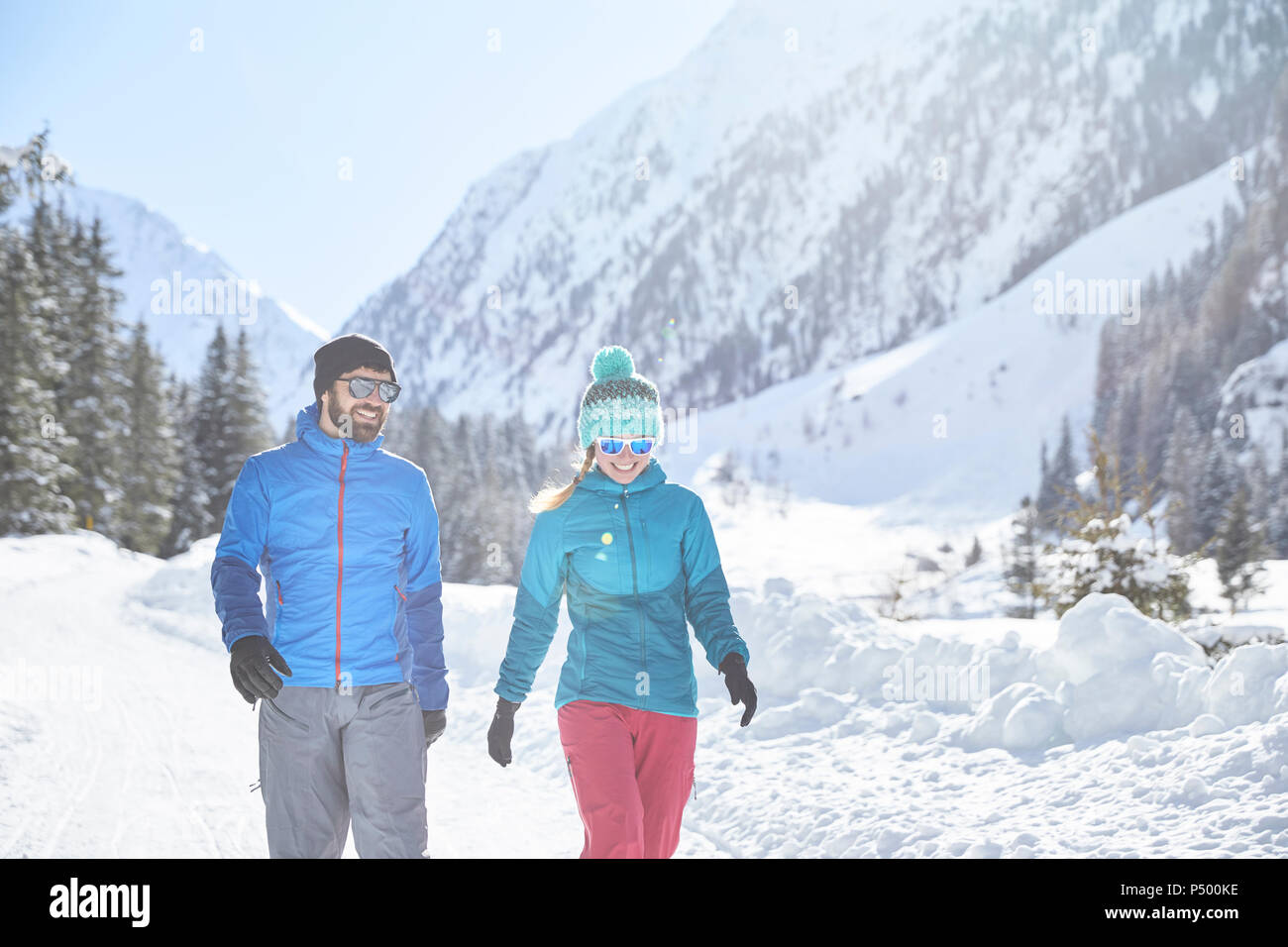 Couple walking in snow-covered landscape - Stock Image