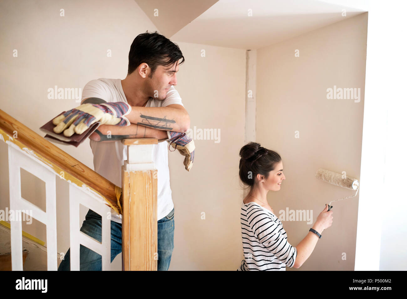 Young couple refurbishing new home, painting staircase - Stock Image
