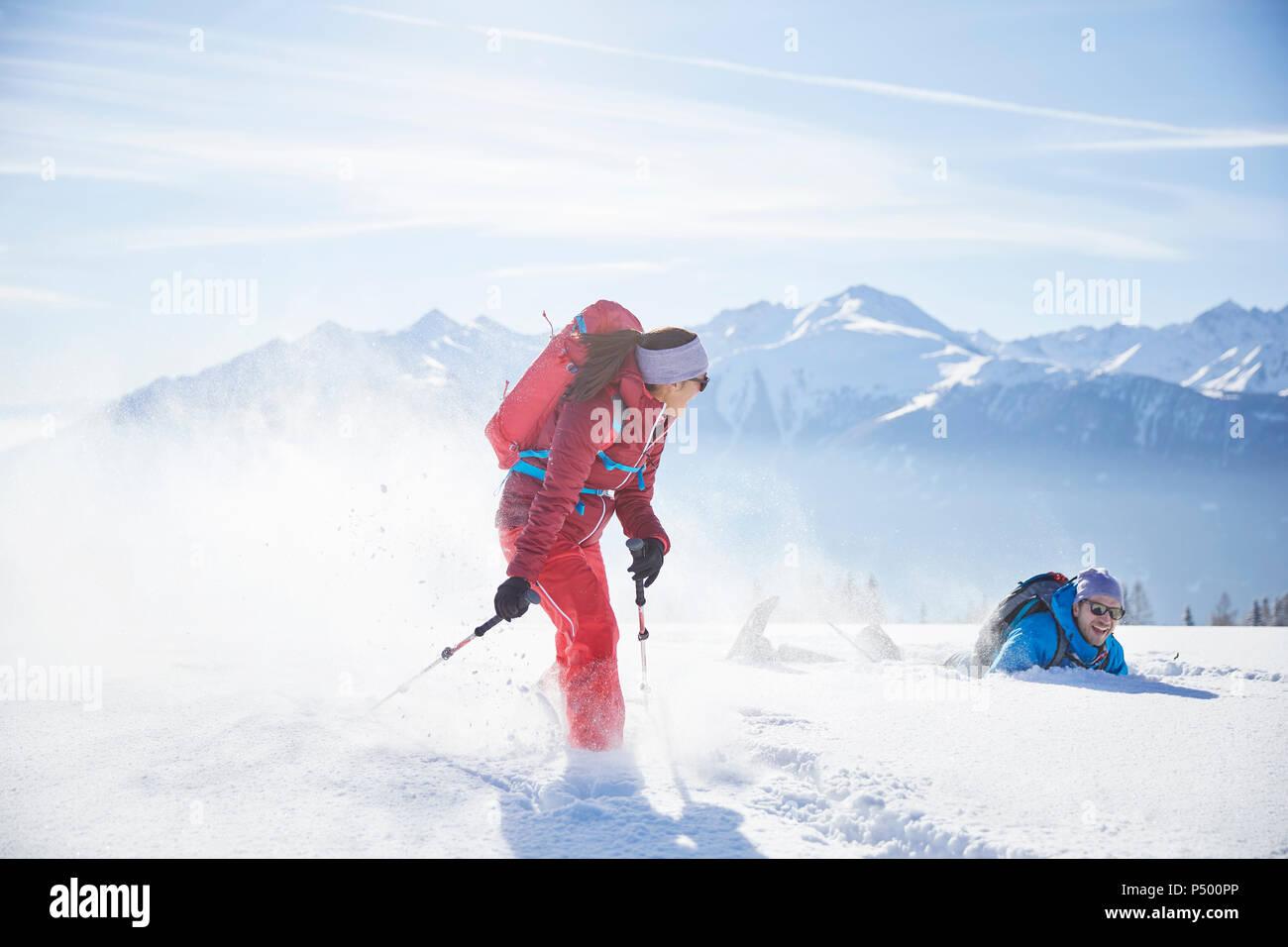 Austria, Tyrol, snowshoe hikers running through snow, man falling - Stock Image