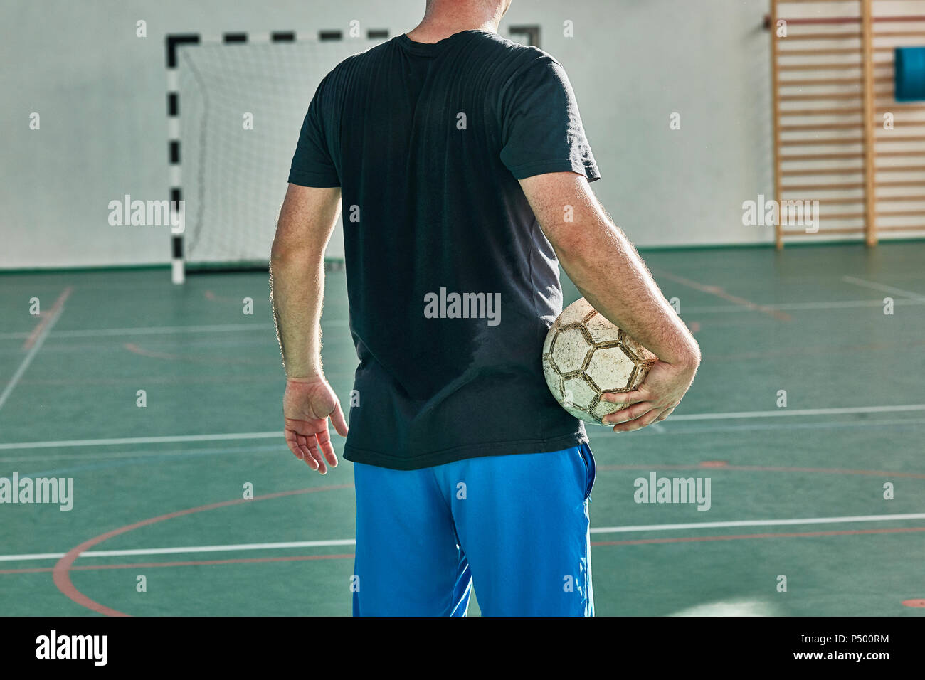 Rear view of indoor soccer player holding the ball - Stock Image