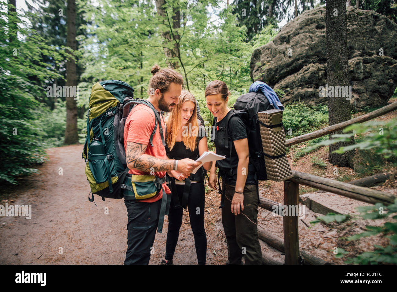 Friends on a hiking trip reading map Stock Photo