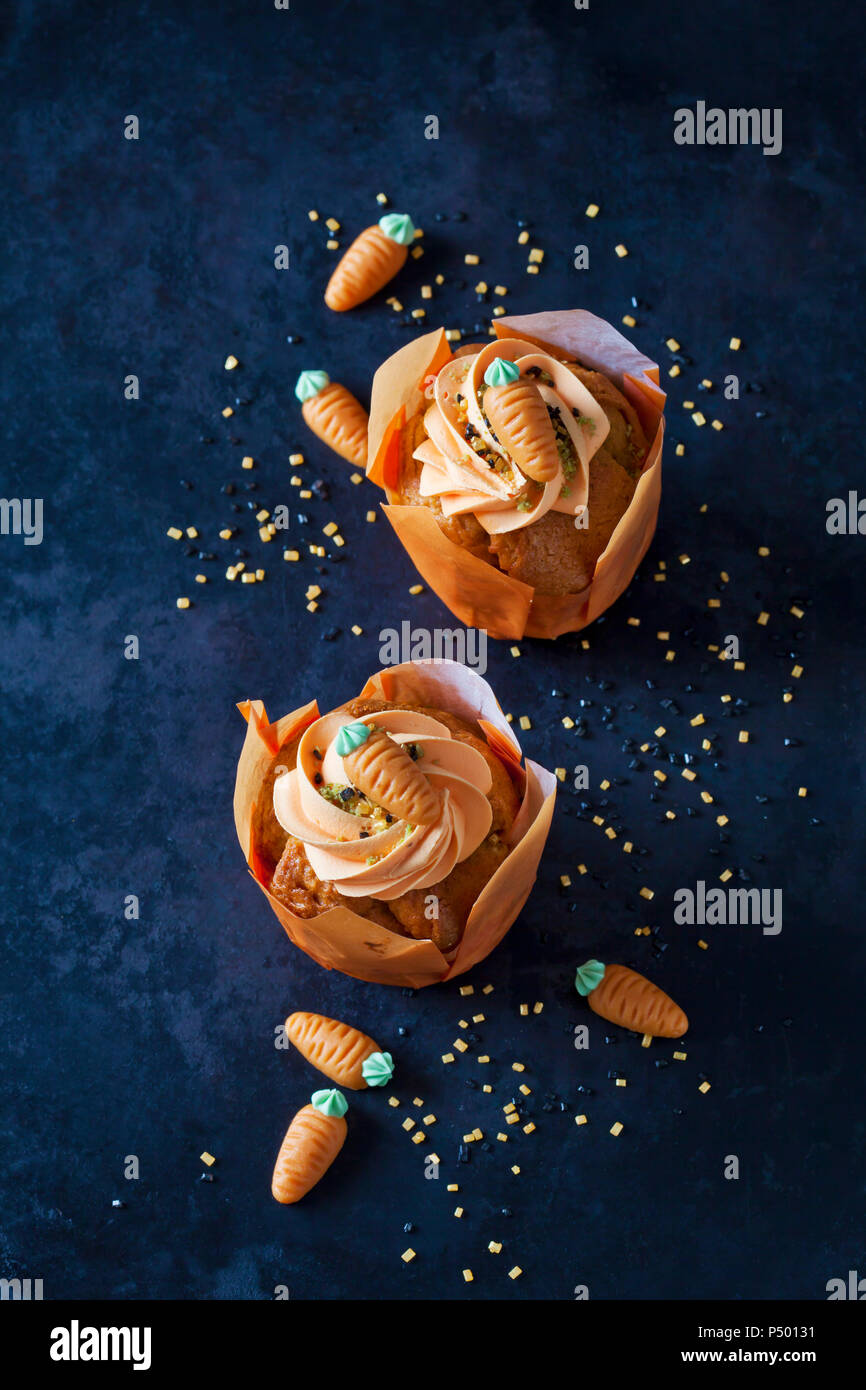 Two carrot cup cakes garnished with  cream topping, sugar granules and marzipan carrots - Stock Image