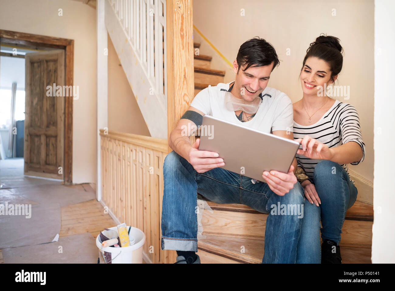 Young couple refurbishing new home, sitting on stairs using digital tablet - Stock Image