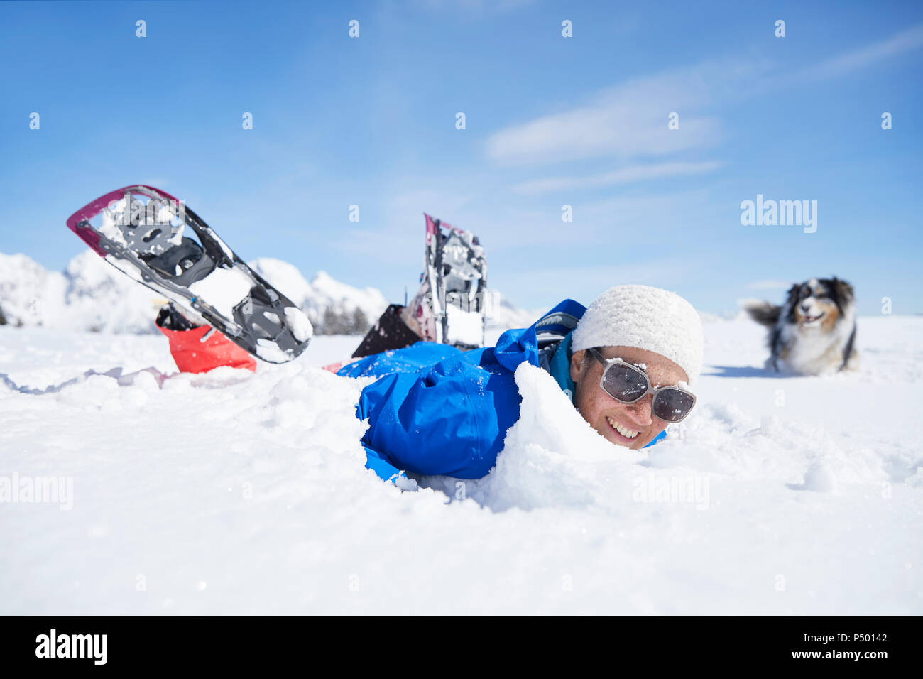 Austria, Tyrol, snowshoe hiker and dog, having fun in the snow Stock Photo
