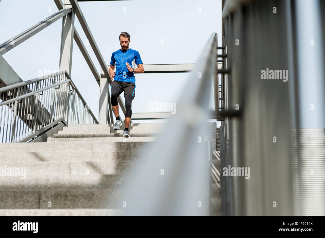 Man running down stairs - Stock Image
