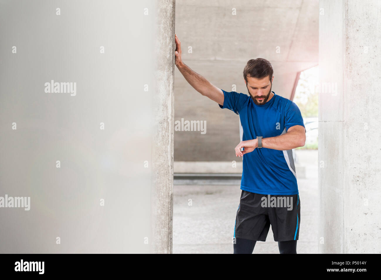 Man having a break from running checking the time - Stock Image
