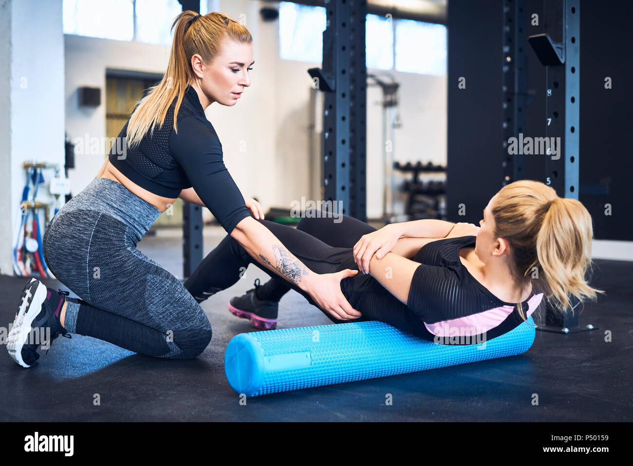Woman massages muscles with personal trainer after gym workout - Stock Image
