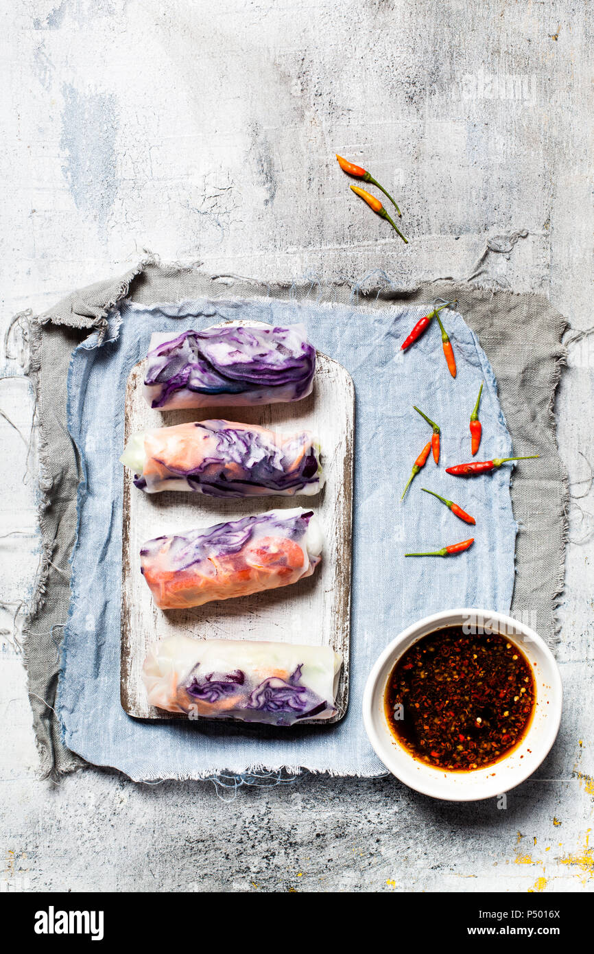 Vegan rice paper wraps (vietnamese summer rolls), filled with cabbage, carrots, bell pepper, rice noodles, and dipping sauce - Stock Image