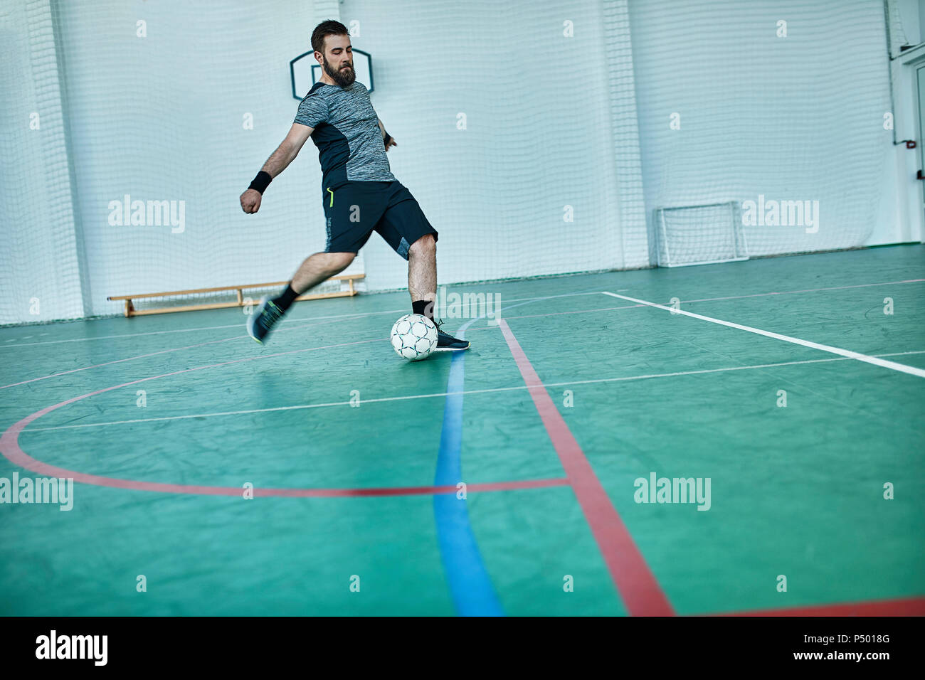 Man playing indoor soccer shooting the ball - Stock Image