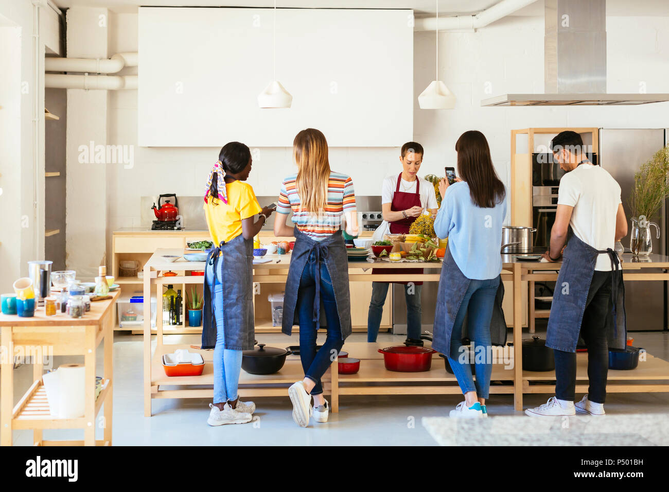 Friends and instructor in a cooking workshop preparing food - Stock Image
