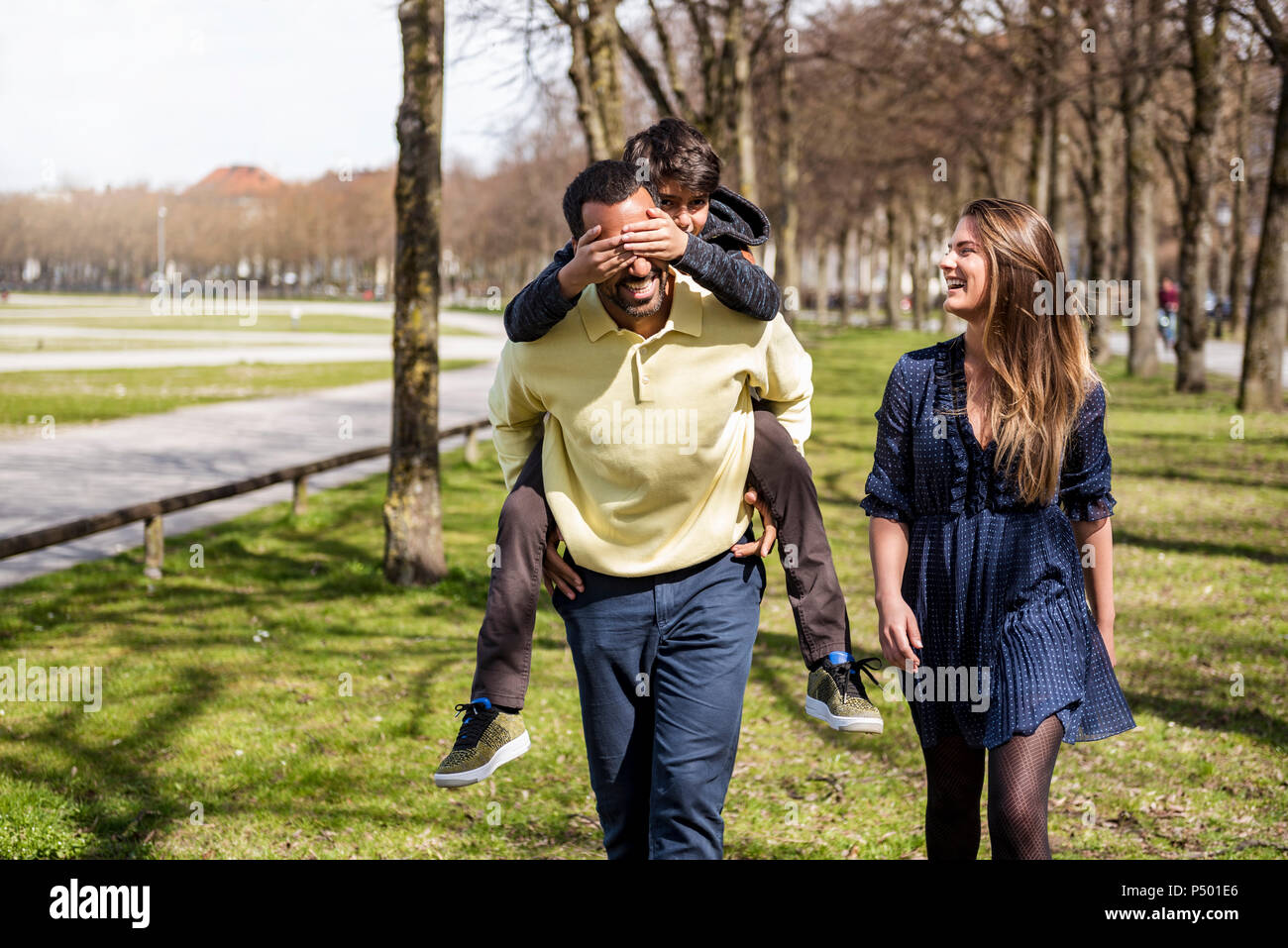Happy family walking in a park - Stock Image