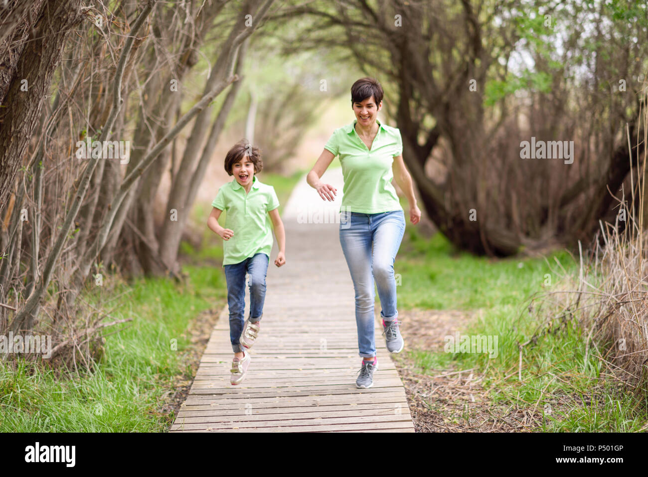 Happy mother and daughter running on boardwalk - Stock Image