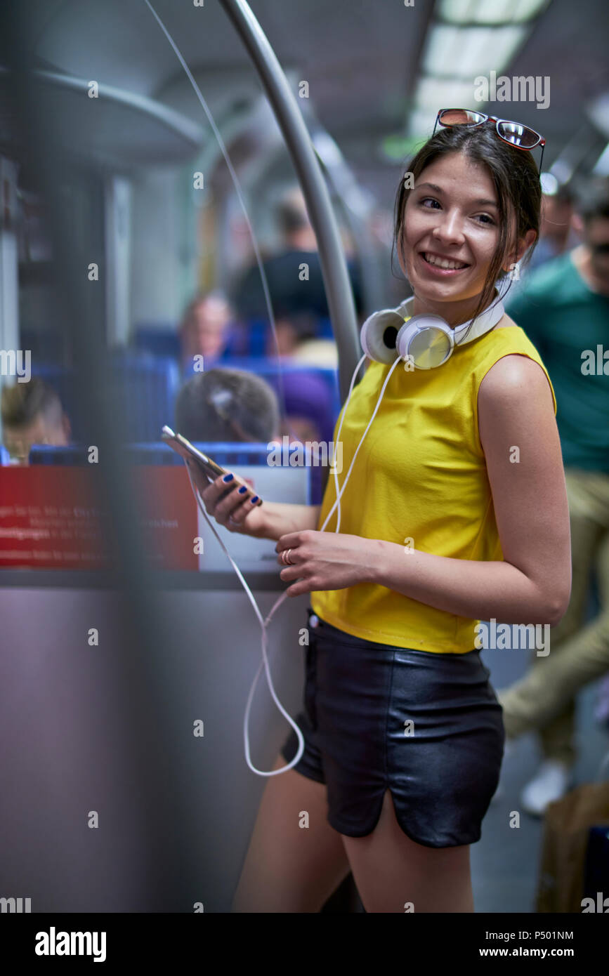 Portrait of smiling young woman with cell phone and headphones in underground train - Stock Image