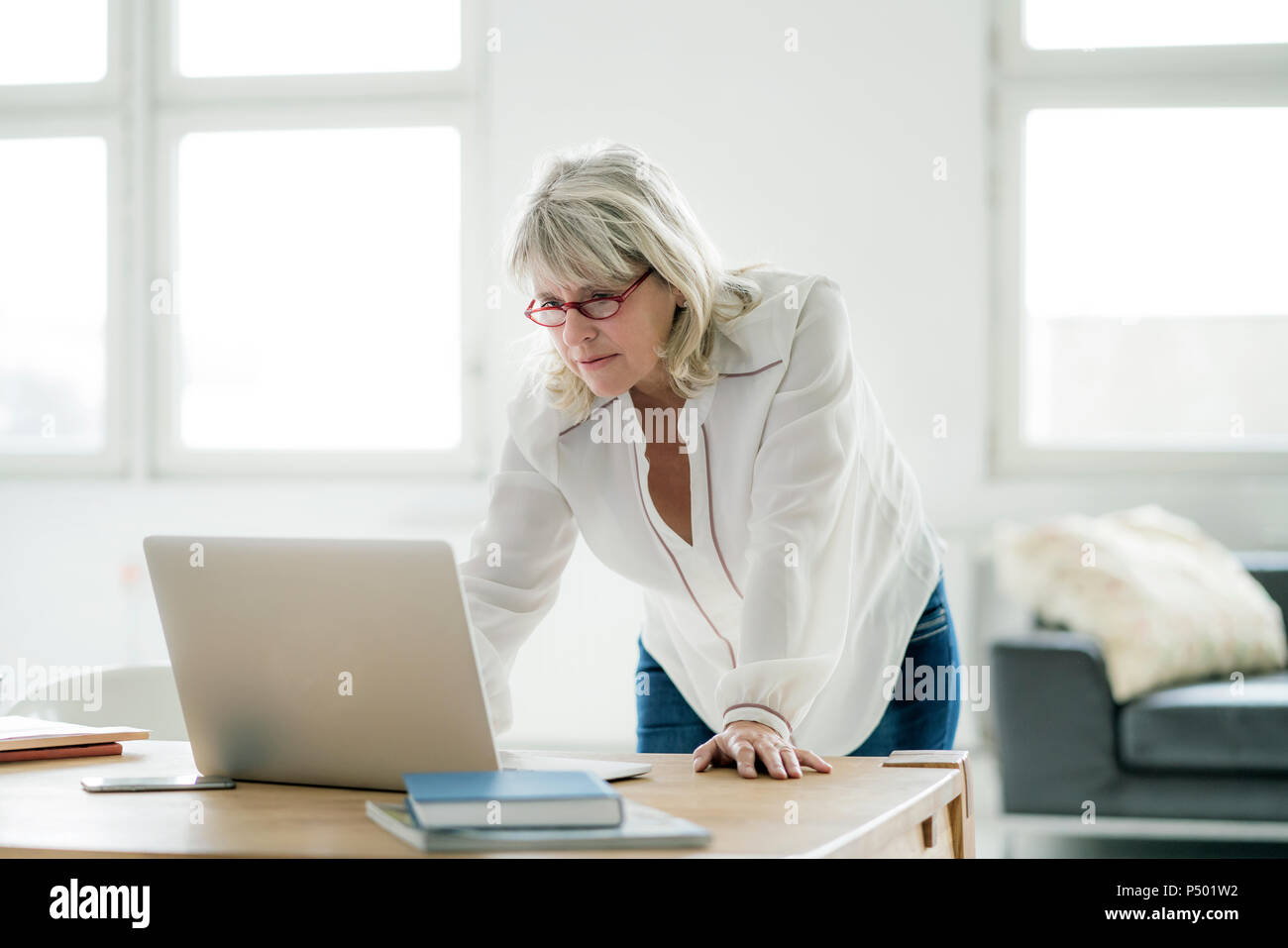 Mature businesswoman working on laptop at desk Stock Photo