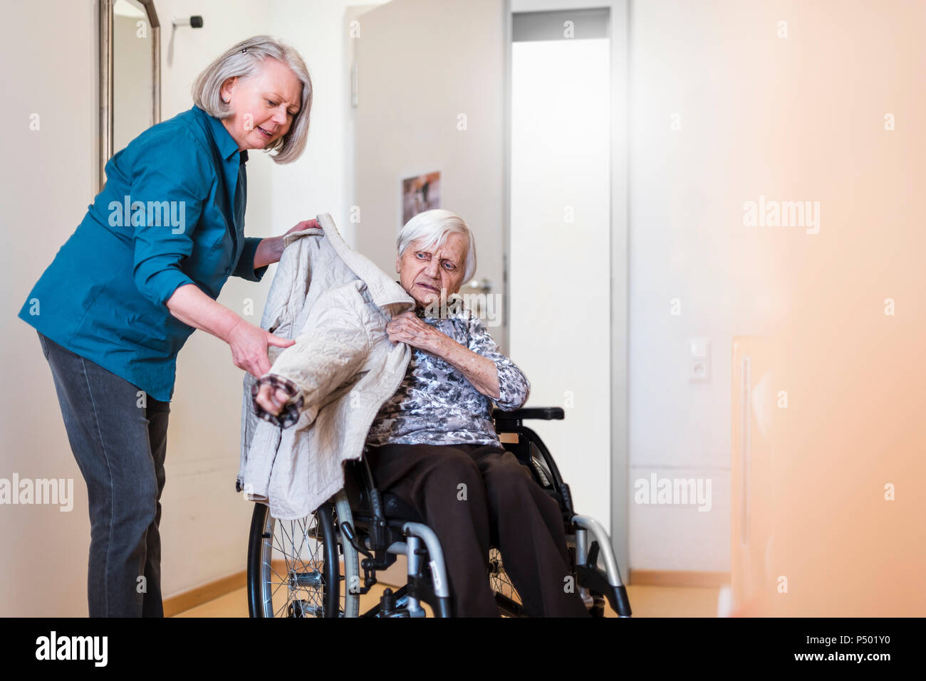 Woman taking care of old woman in wheelchair putting her jacket on - Stock Image