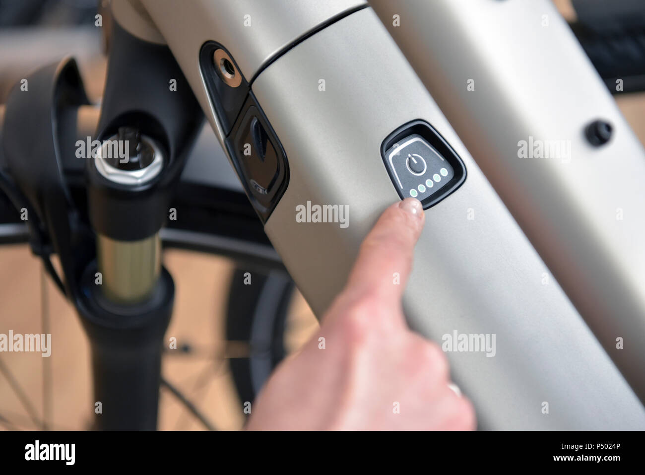 Finger pointing on switch of an e-bike - Stock Image