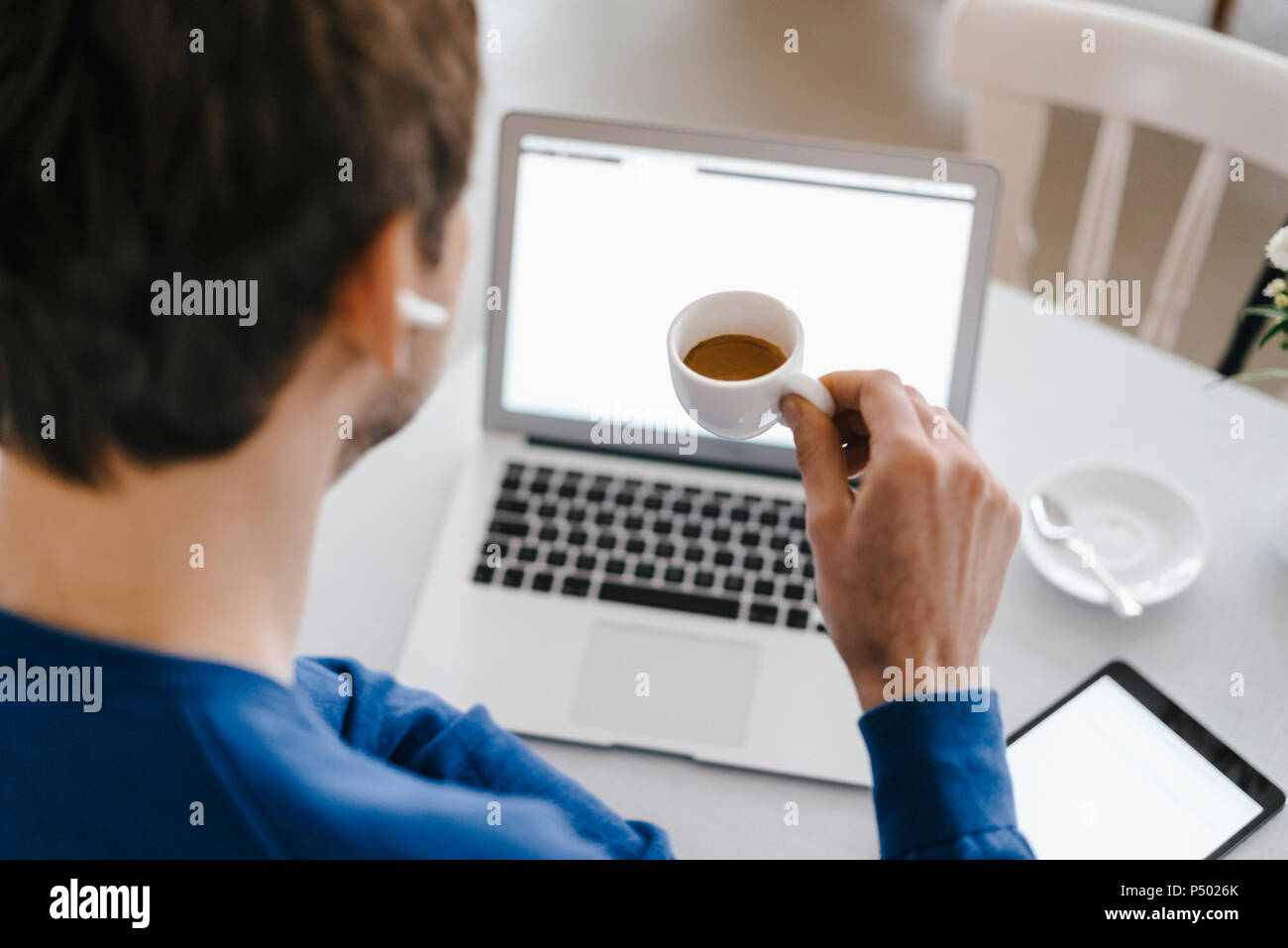 Close-up of man in a cafe using laptop and drinking coffee - Stock Image