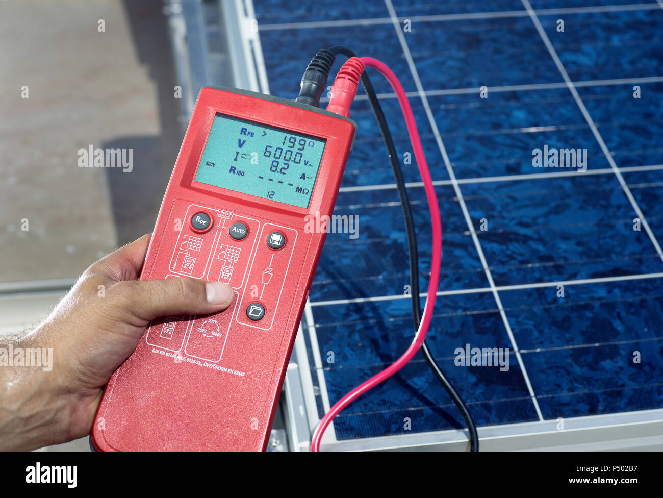 Man's hand holding measuring device in front of solar plant, close-up - Stock Image