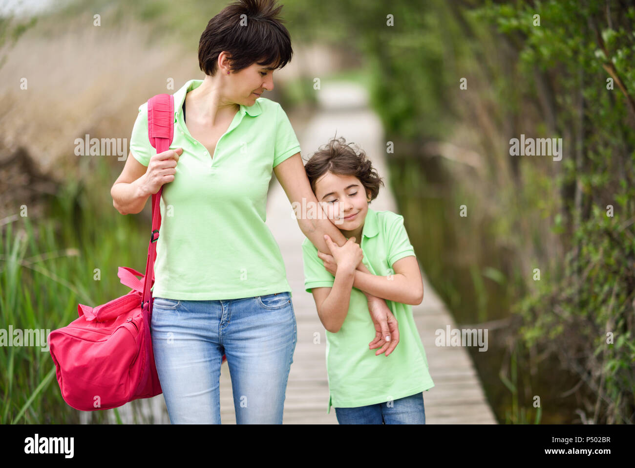 Mother and affectionate daughter walking on boardwalk - Stock Image