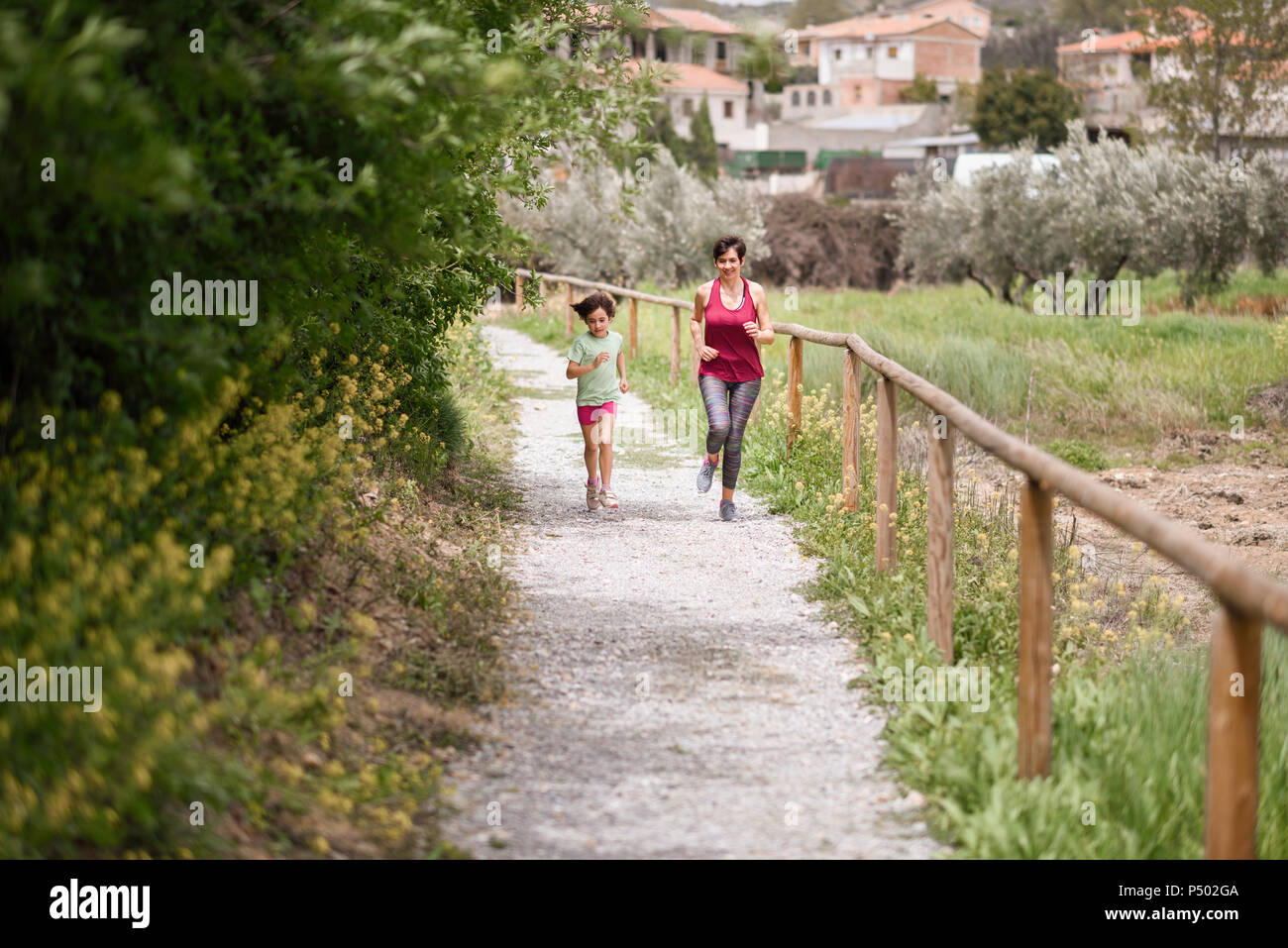 Mother and daughter running on a path in nature enviroment - Stock Image
