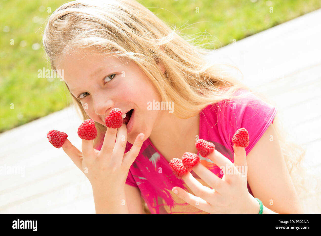 Portrait of smiling girl with raspberries on  fingers Stock Photo