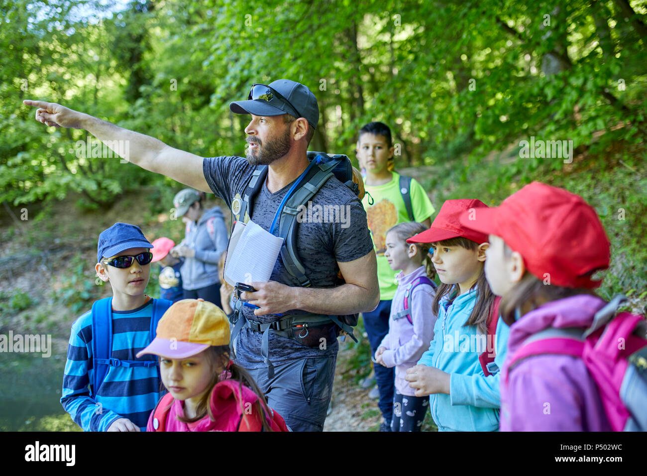Man talking to kids on a field trip in forest - Stock Image