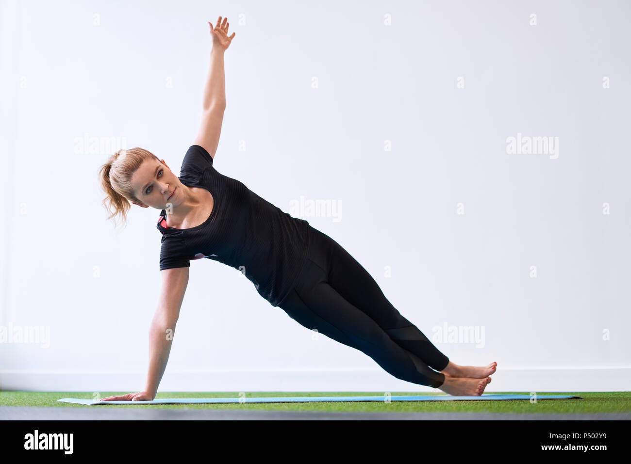 Woman doing side plank yoga exercise in studio - Stock Image