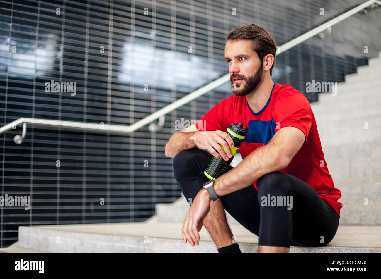 Man sitting on stairs having a break from running - Stock Image