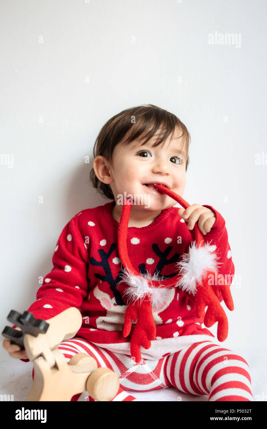86f58ac1e38e2 Portrait of smiling baby girl with reindeer antlers headband at Christmas  time - Stock Image
