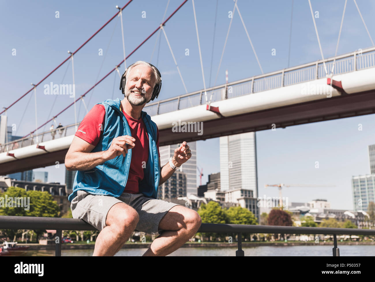 Happy athletic mature man with headphones sitting at the riverside in the city - Stock Image