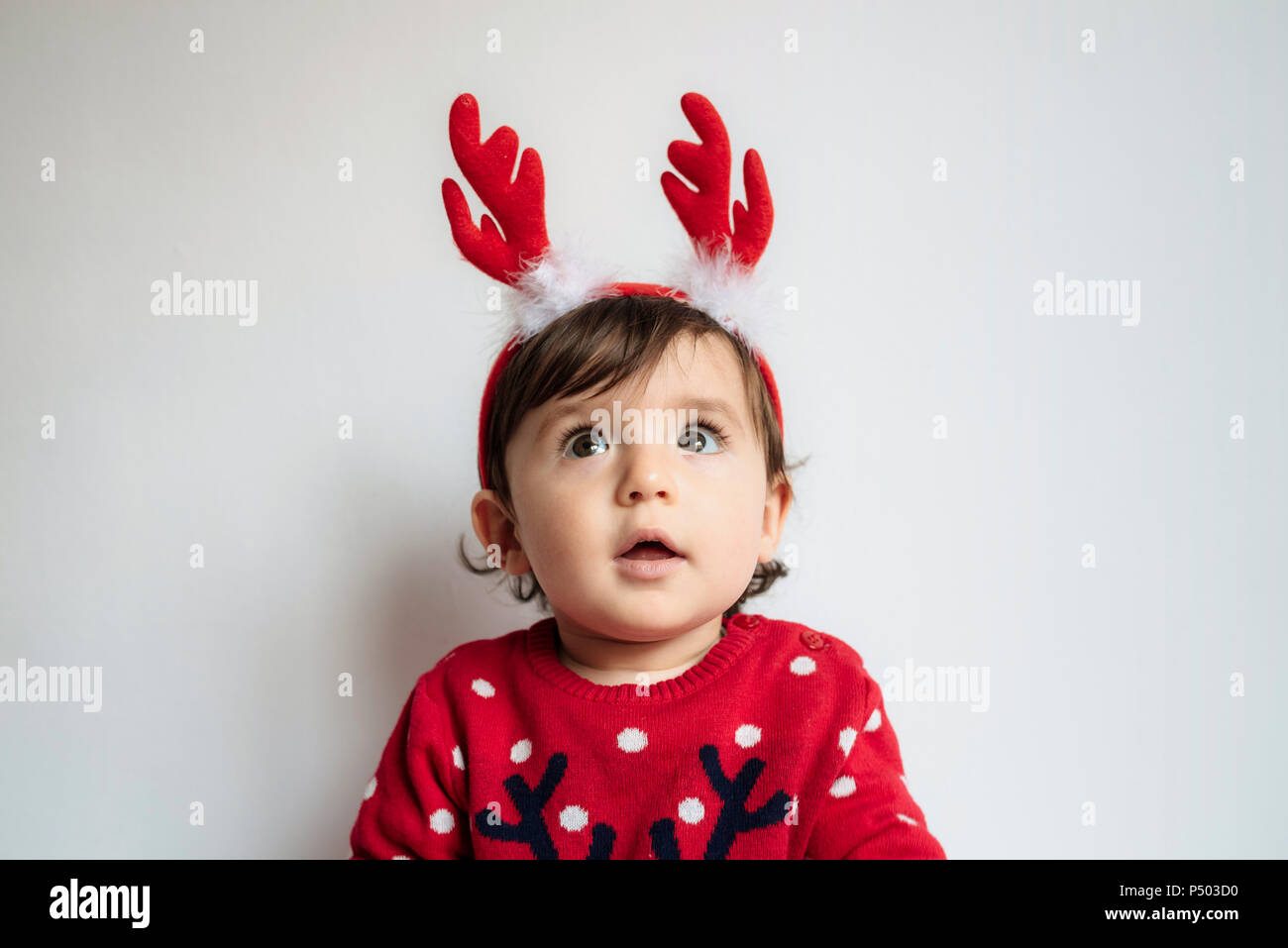 a3dfd43e8f02e Portrait of astonished baby girl wearing reindeer antlers headband - Stock  Image