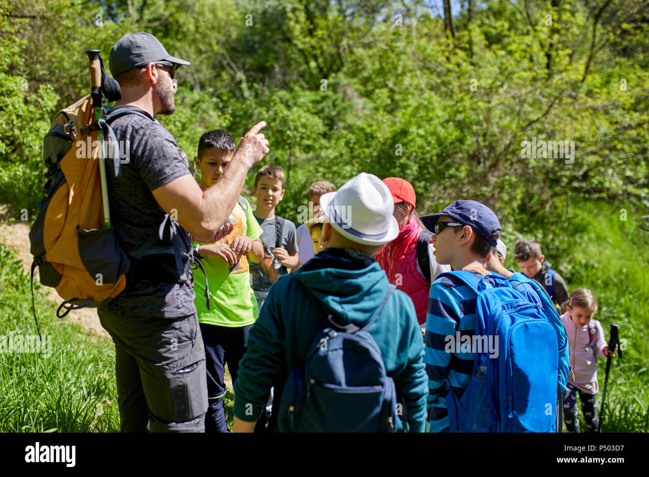 Man talking to kids on a field trip on trail Stock Photo