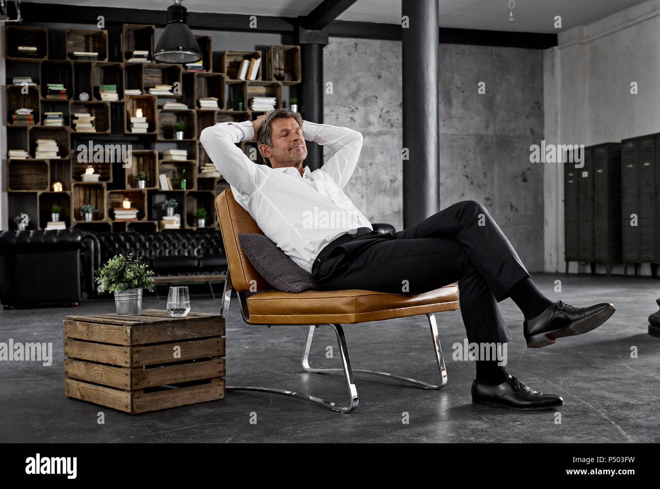 Mature man sitting on chair in loft relaxing - Stock Image