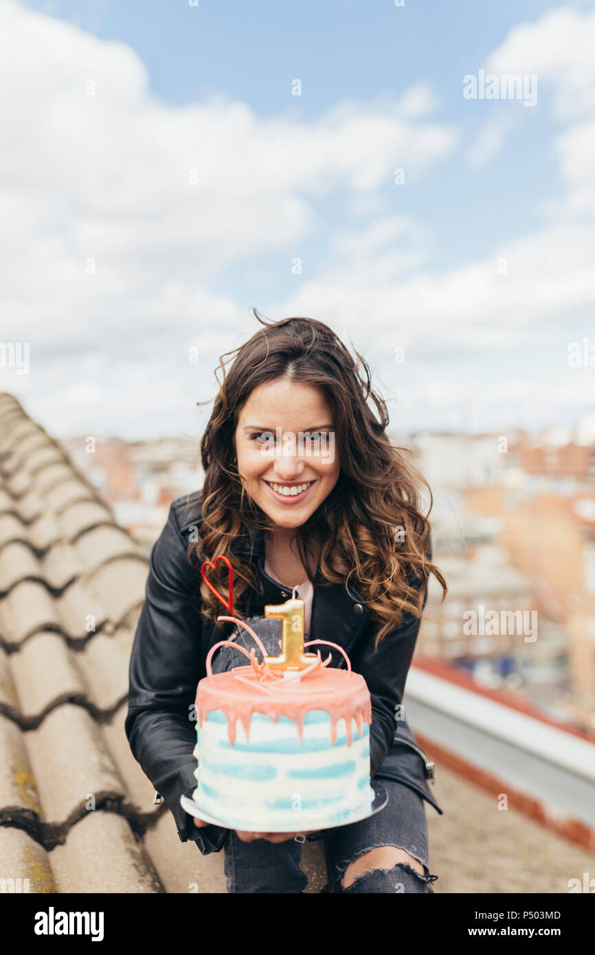 Portrait Of Woman Presenting Birthday Cake On Roof