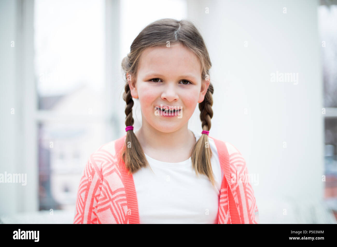 Portrait of smiling girl with braids - Stock Image