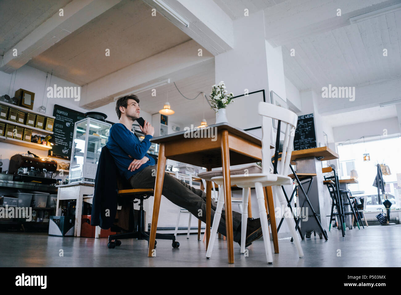 Man sitting at table in a cafe thinking - Stock Image