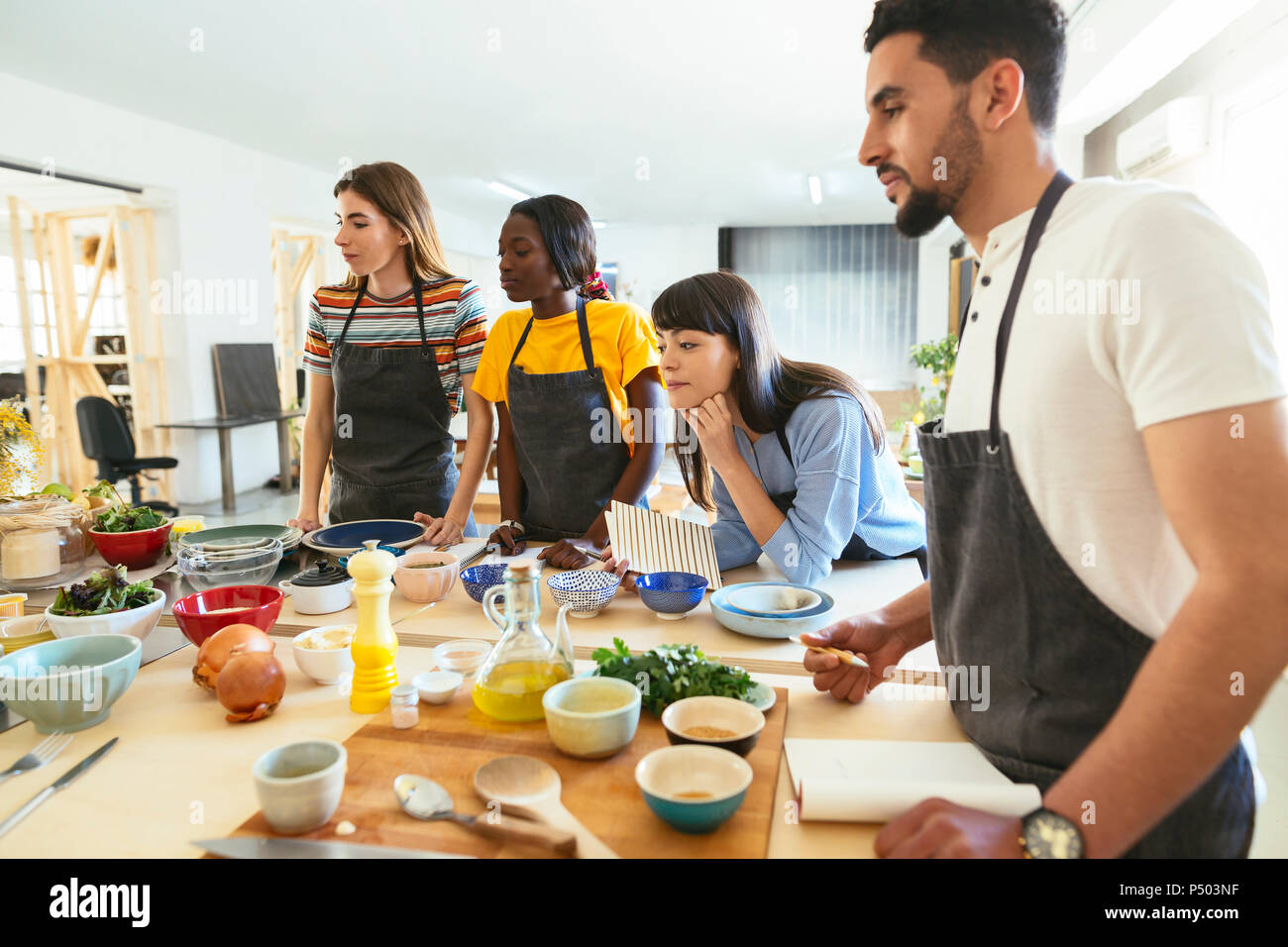Friends in a cooking workshop watching attentively - Stock Image