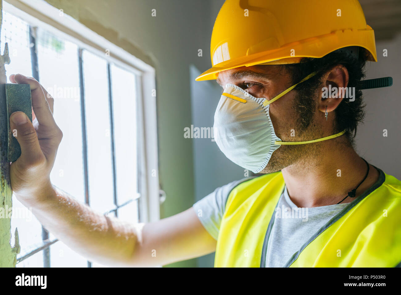 Close-up of worker sanding wooden window - Stock Image