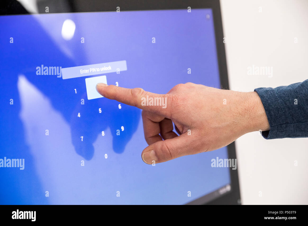 Businessman entering PIN code on touch screen - Stock Image