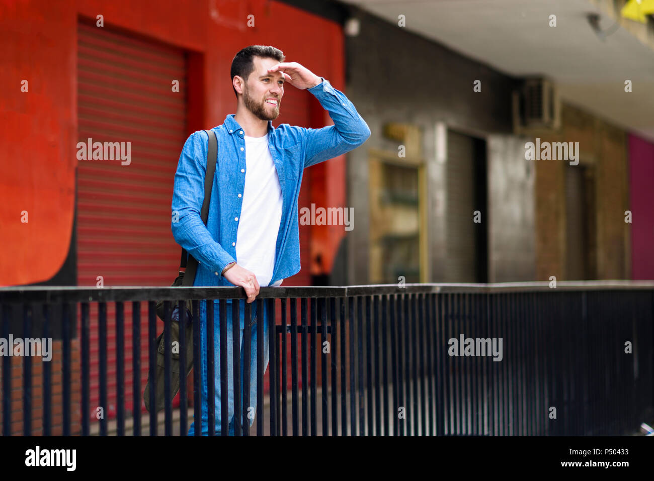 Young man standing in the city, looking at distance, shielding eyes - Stock Image