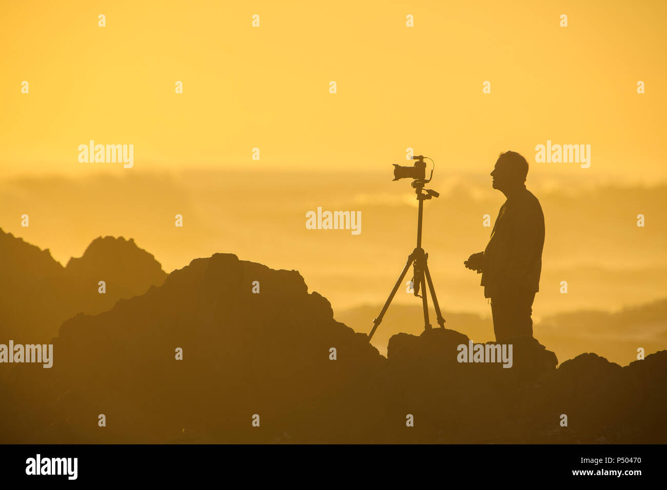 Africa, South Africa, Cape Town, Silhouette of photographer at beach in the evening light - Stock Image