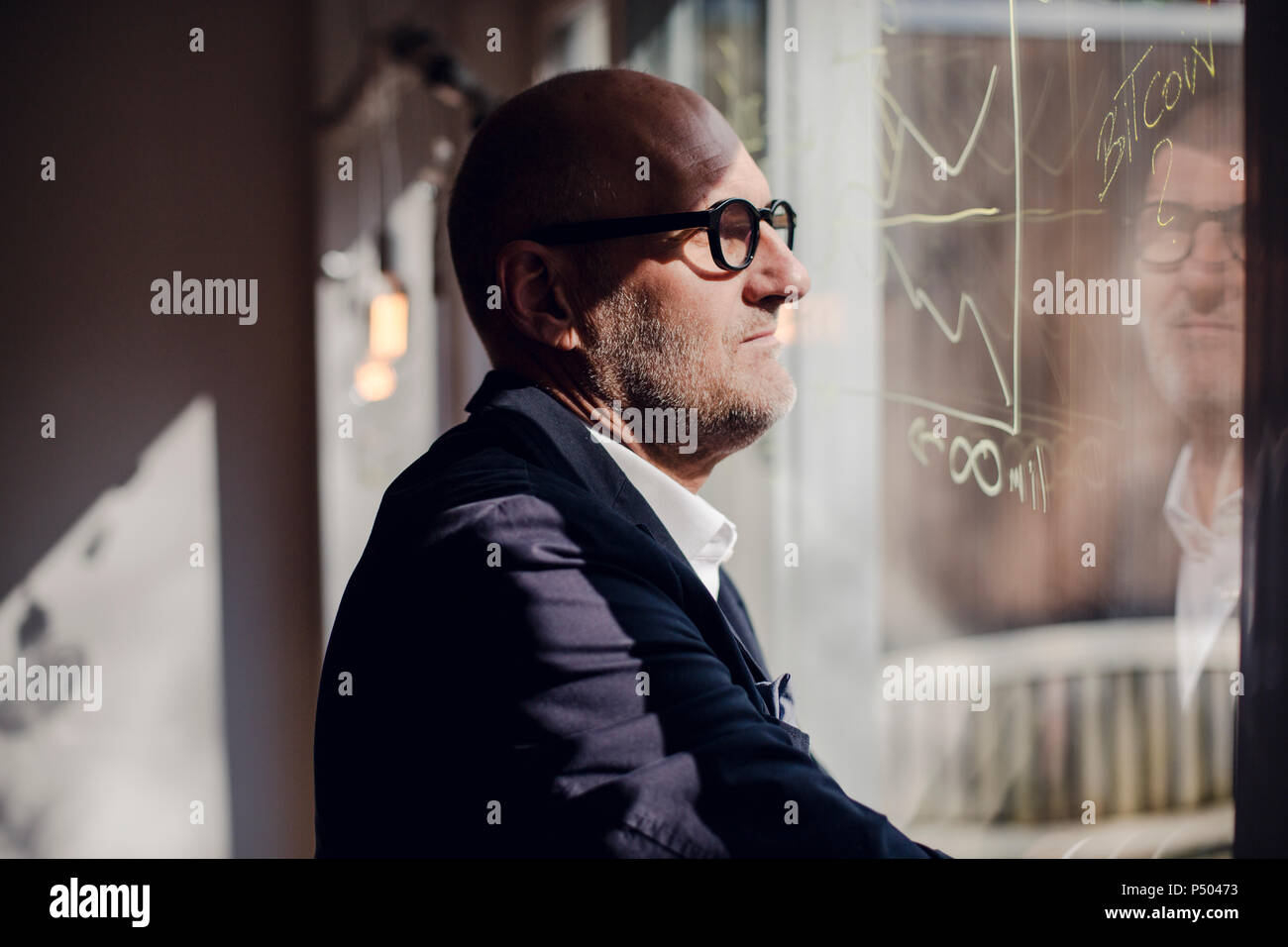 senior businessman brainstorming, drawing formulas on window pane - Stock Image