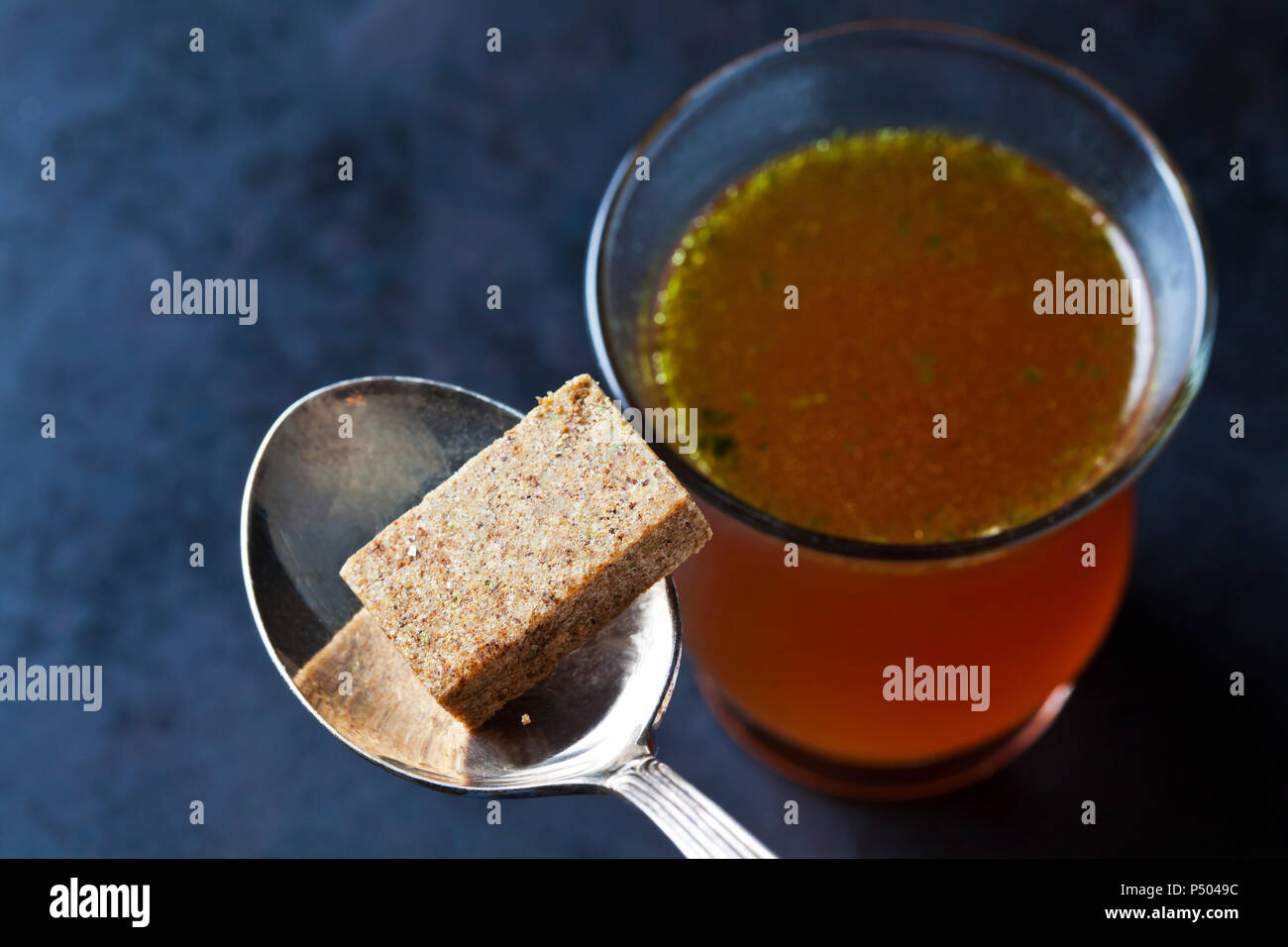 Glass of stock and stock cube on tea spoon - Stock Image