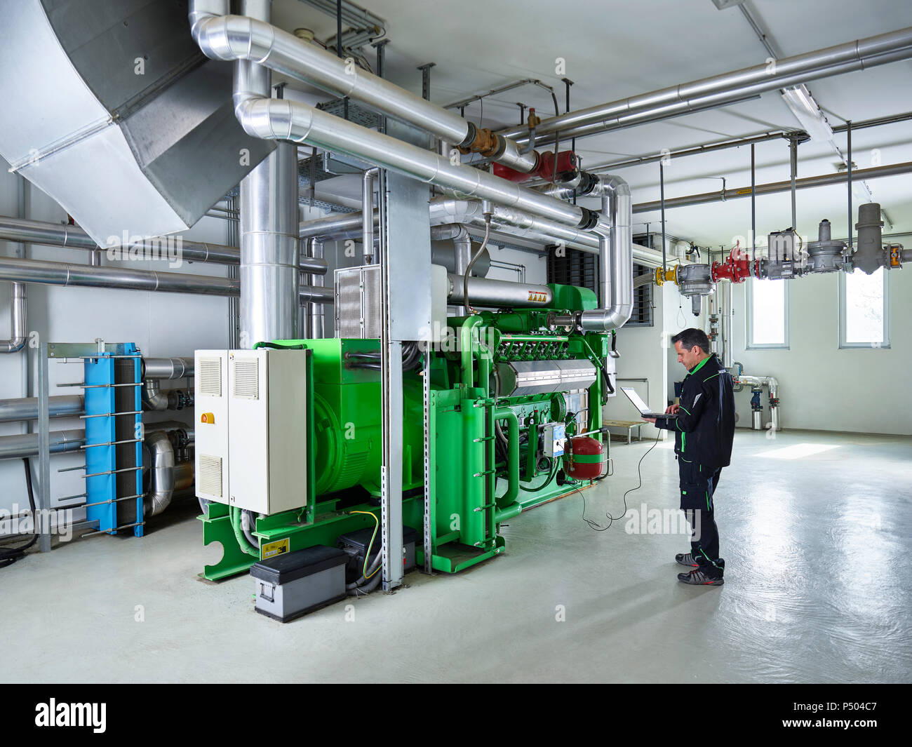 Combined heat and power plant, worker using laptop in front of gas engine - Stock Image